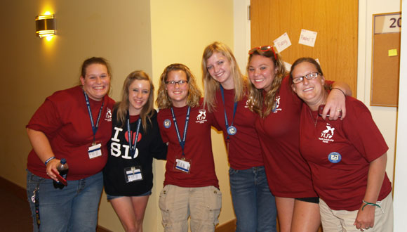 A group of female delegates from the 2012 Kansas YLF link arms and smile for a photo outside of their dorm.